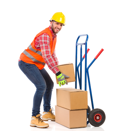 push cart: Manual worker  picking up a carton box from push cart. Full length studio shot isolated on white.