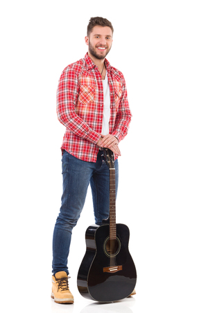 lumberjack shirt: Guitarist in red lumberjack shirt posing with a black acoustic guitar. Full length studio shot isolated on white.