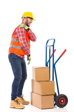 accidente trabajo: trabajador manual que sostiene el hombro en el dolor. Estudio de longitud completa aislado disparo en blanco.