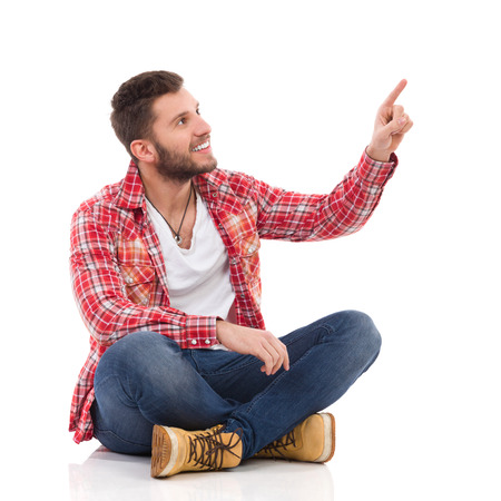 Handsome young man in jeans and lumberjack shirt sitting on floor with legs crossed and pointing up. Full length studio shot isolated on white. Standard-Bild