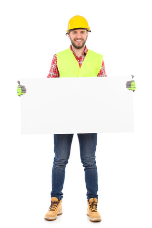 Construction worker in yellow helmet and reflective waistcoat holding white placard. Full length studio shot isolated on white. Standard-Bild