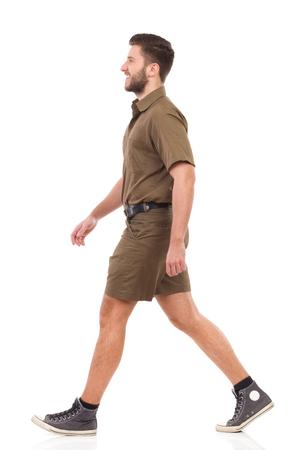 from side: Happy man in khaki uniform walking. Full length studio shot isolated on white.