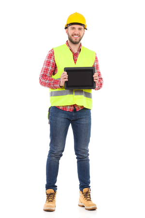 clothes organizer: Smiling manual worker in yellow helmet and lime waistcoat holding shockproof digital tablet in both hands. Full length studio shot isolated on white. Stock Photo