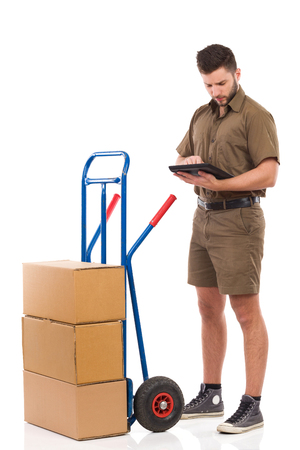 push cart: Focused courier standing close to push cart and reading something on a digital tablet. Full length studio shot isolated on white. Stock Photo