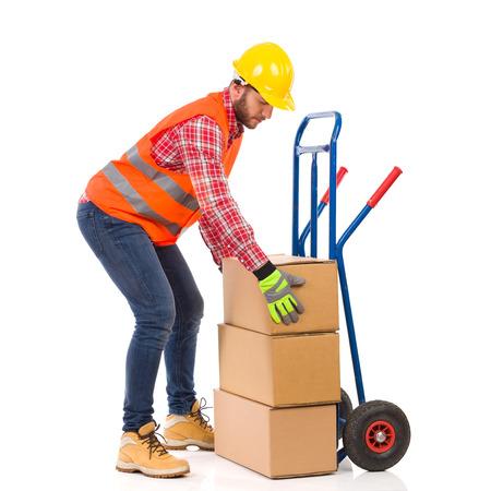 push cart: Manual worker arranges carton box on a push cart. Full length studio shot isolated on white.
