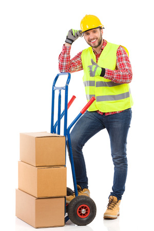 Smiling manual worker lean on the push cart and showing thumb up. Full length studio shot isolated on white. Stock Photo - 53888616