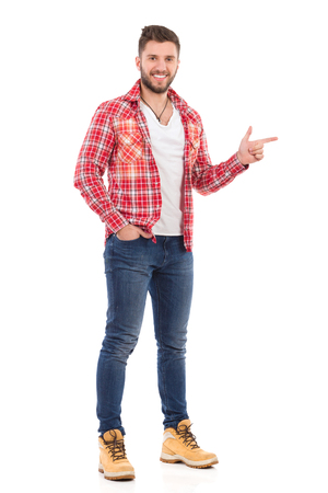 Smiling handsome young man in jeans and lumberjack shirt standing and pointing. Full length studio shot isolated on white.