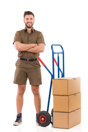 mover: Happy messenger or mover standing with arms crossed close to delivery cart. Full length studio shot isolated on white.