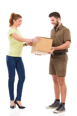 Smiling female receives package from courier. Full length studio shot isolated on white. Standard-Bild
