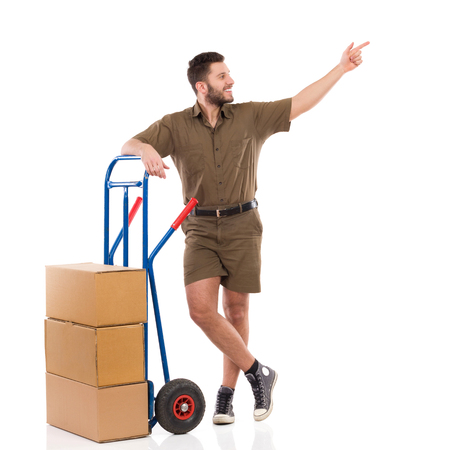 leaning on the truck: Cheerful delivery man standing relaxed with a push pointing and looking away. Full length studio shot isolated on white.