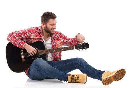 lumberjack shirt: Guitarist in red lumberjack shirt sitting on a floor and tune the black acoustic guitar. Full length studio shot isolated on white.