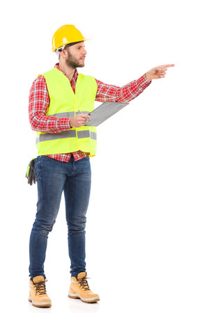 Manual worker in yellow helmet and lime vest holding a clipboard and pointing. Full length studio shot isolated on white.