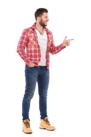 lumberjack shirt: Smiling handsome young man in jeans and lumberjack shirt, pointing and looking away. Full length studio shot isolated on white.