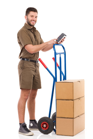 push cart: Smiling courier standing next to push cart and posing with a scanner. Full length studio shot isolated on white.