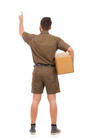 service man: Man in brown uniform holding package under his arm and pointing up. Rear view. Full length studio shot isolated on white.