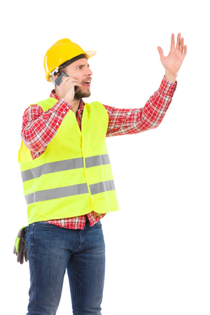 three quarter length: Angry manual worker in yellow helmet and lime waistcoat using phone and gesturing. Three quarter length studio shot isolated on white. Stock Photo