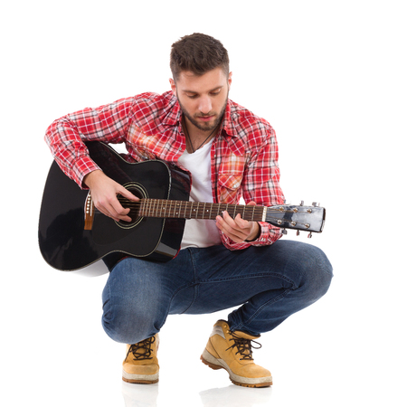 lumberjack shirt: Guitarist in red lumberjack shirt crouching and play the black acoustic guitar. Full length studio shot isolated on white. Stock Photo