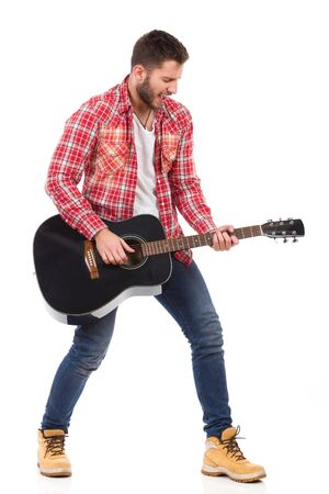 legs apart: Guitarist in red lumberjack shirt standing with legs apart and play the black acoustic guitar. Full length studio shot isolated on white.