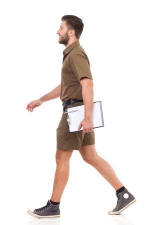 from side: Happy man in khaki uniform walking and carrying clipboard. Full length studio shot isolated on white. Stock Photo