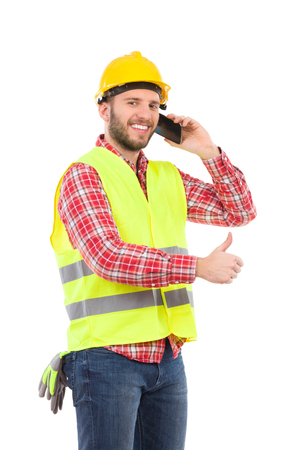 Smiling construction worker in yellow helmet and lime waistcoat posing with cell phone and showing thumb up. Three quarter length studio shot isolated on white. Standard-Bild