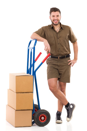 leaning on the truck: Cheerful delivery man standing relaxed with a push cart. Full length studio shot isolated on white.
