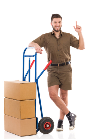 leaning on the truck: Smiling delivery man standing relaxed with a push cart and pointing up. Full length studio shot isolated on white. Stock Photo