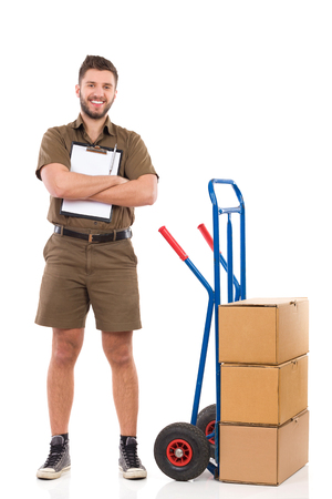 mover: Happy delivery man or mover standing with arms crossed and holding a clipboard. Full length studio shot isolated on white.