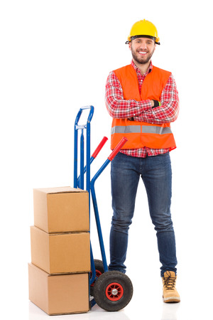 reflective vest: Smiling man in yellow hardhat and orange reflective vest posing with arms crossed next to delivery cart. Full length studio shot isolated on white.