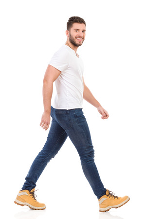 profile view: Smiling man in jeans and white t-shirt walking and looking at camera. Full length studio shot isolated on white.