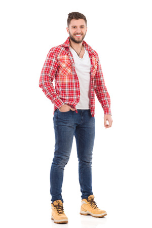 Smiling young man in jeans and lumberjack shirt standing with hand in pocket. Full length studio shot isolated on white.