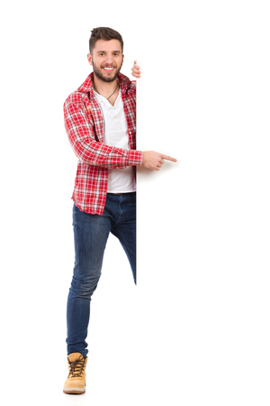 Handsome young man in jeans and lumberjack shirt standing behind white banner and pointing. Full length studio shot isolated on white.