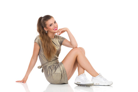 side shot: Smiling attractive girl in gold mini dress and white sneakers sitting on floor and looking at camera. Side view, Full length studio shot isolated on white.