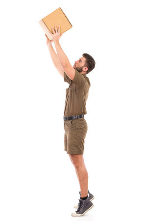 Delivery man in khaki uniform picking up a carton box. Full length studio shot isolated on white.