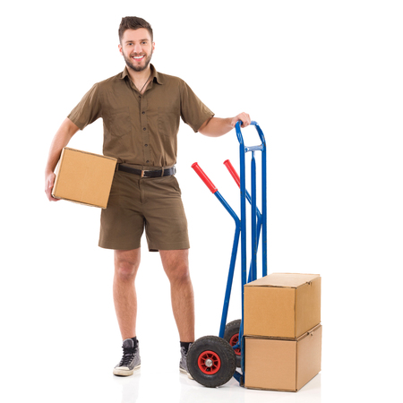 push cart: Happy courier standing close to push cart and holding package under his arm. Full length studio shot isolated on white.