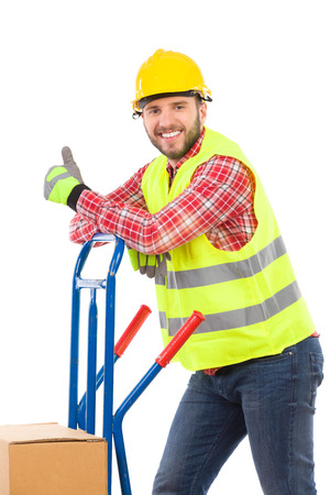 three quarter: Smiling manual worker lean on the push cart and showing thumb up. Three quarter length studio shot isolated on white.