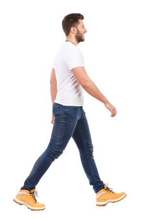 side view: Smiling man walking in jeans and white t-shirt. Full length studio shot isolated on white.