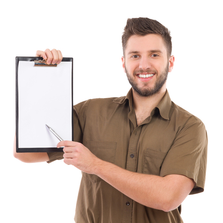 waist shot: Happy courier holding a clipboard in one hand and pointing with a pen. Waist up studio shot isolated on white.
