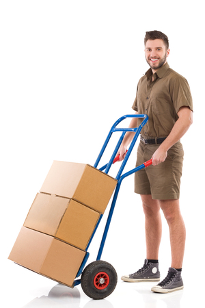 Happy delivery man standing with a push cart. Full length studio shot isolated on white.