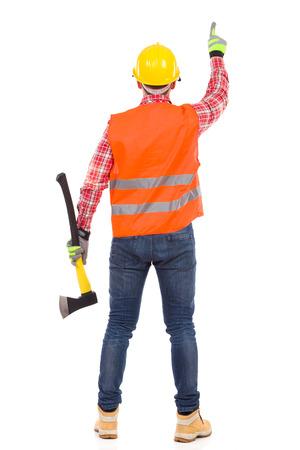 Lumberjack dans le casque jaune et gilet orange, debout avec une hache et de pointage, Vue arrière. La pleine longueur tourné en studio isolé sur blanc.