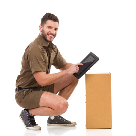 clothes organizer: Happy delivery man crouching close to carton box and holding digital tablet. Full length studio shot isolated on white.