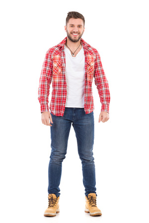 Handsome young man in jeans and lumberjack shirt standing and smiling. Full length studio shot isolated on white.