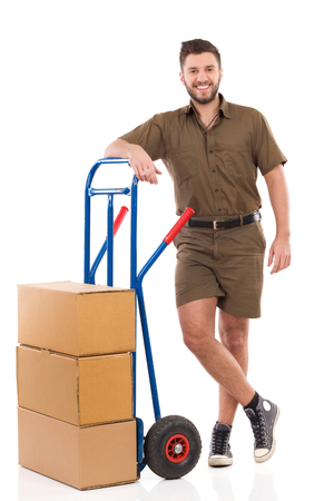 push cart: Happy delivery man or mover standing with legs crossed at ankle close to push cart. Full length studio shot isolated on white.