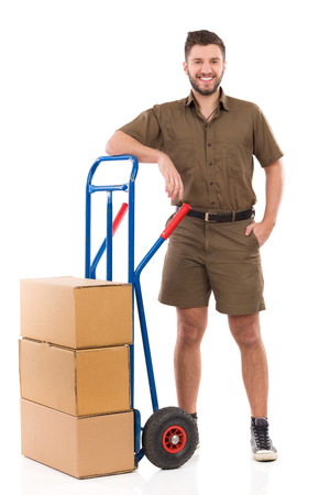 push cart: Happy delivery man or mover standing relaxed close to push cart. Full length studio shot isolated on white.