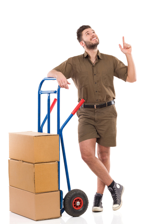 leaning on the truck: Cheerful delivery man standing relaxed with a push cart and pointing up. Full length studio shot isolated on white. Stock Photo