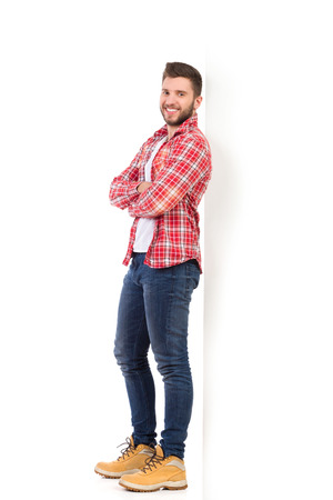 Smiling handsome young man in jeans and lumberjack shirt  lean on the wall with arms crossed. Full length studio shot isolated on white.
