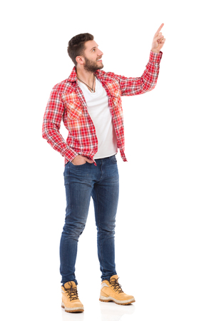 Smiling handsome young man in jeans and lumberjack shirt standing and pointing up. Full length studio shot isolated on white.