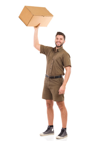Happy delivery man standing and holding carton box in raised hand. Full length studio shot isolated on white. Standard-Bild