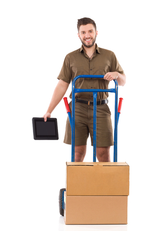 leaning on the truck: Cheerful delivery man standing behind a push cart and holding digital tablet. Full length studio shot isolated on white.