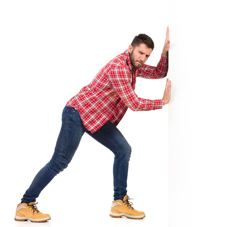 lumberjack shirt: Handsome young man in jeans and lumberjack shirt pushing a white banner. Full length studio shot isolated on white.