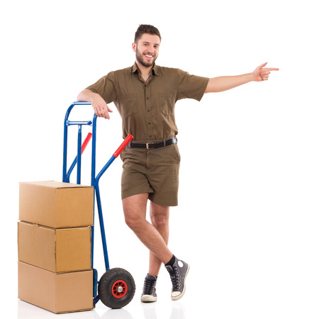 leaning on the truck: Cheerful delivery man standing relaxed with a push cart and pointing. Full length studio shot isolated on white.